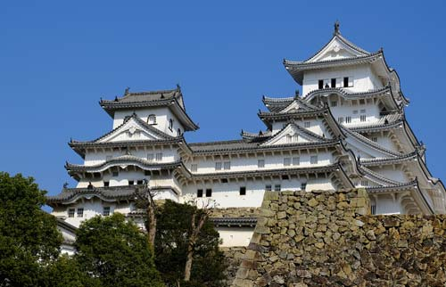 white tiers of a japanese castle against a blue sky