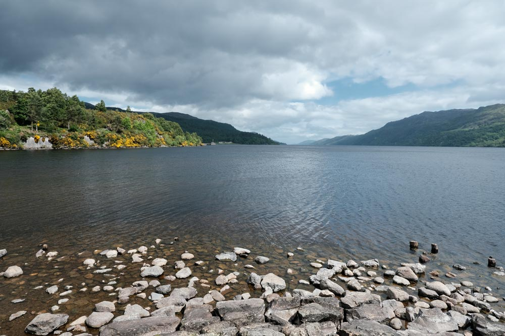 calm water of lake with stones in foreground
