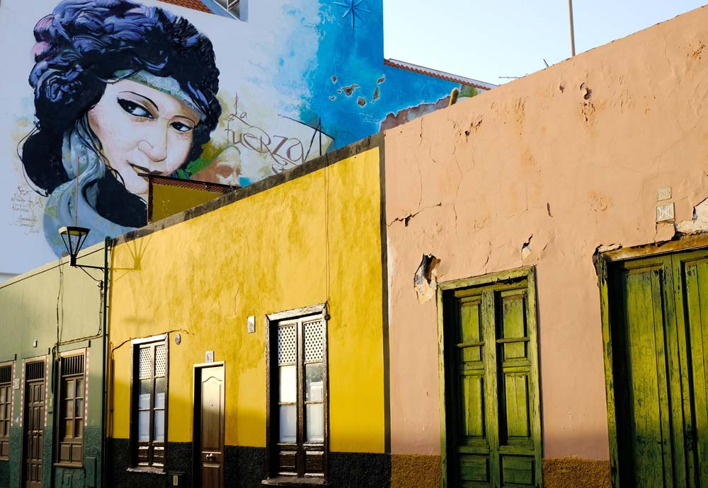 ochre coloured buildings and mural of womans face