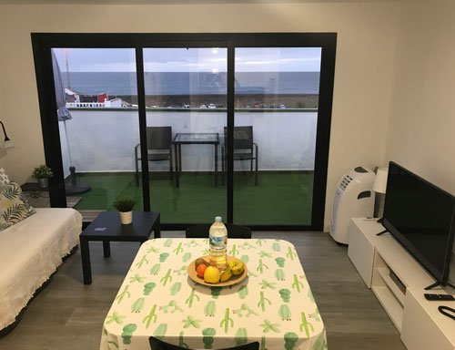 lounge with table with fruit bowl and terrace overlooking sea