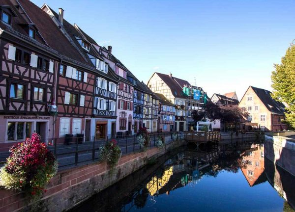 gabled-buidlings reflected in still water of canal in colmar in france
