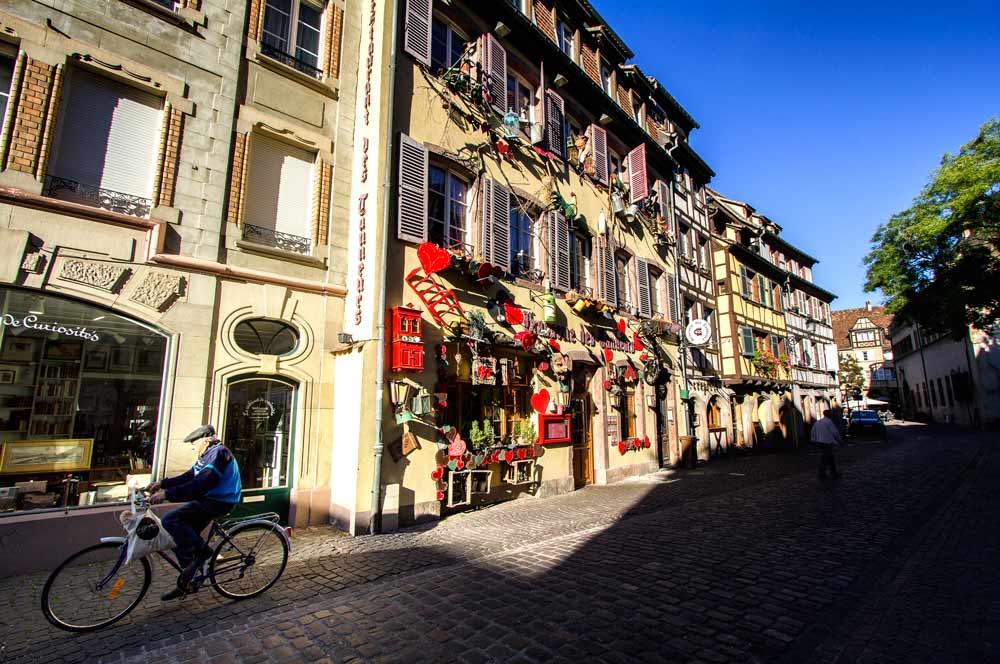 man riding bike along medieval street in colmar france