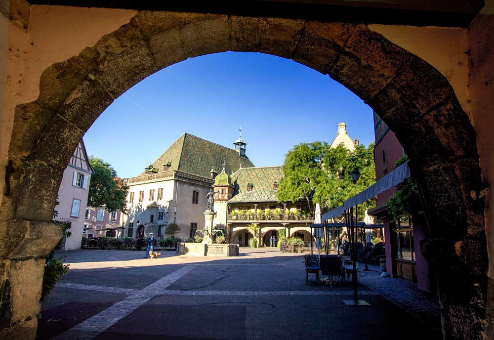 medieval square viewed through stone arch
