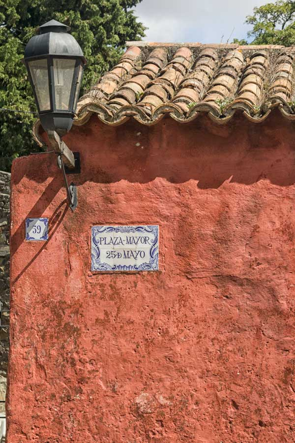 side of ochre stone colonial building with spanish street sign