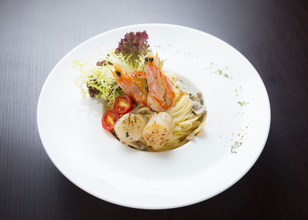 seafood, spaghetti and tomatoes on a plate