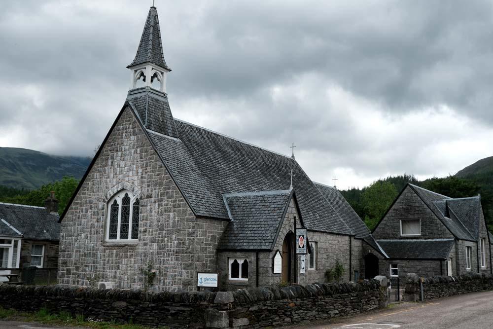old grey stone church building on village street