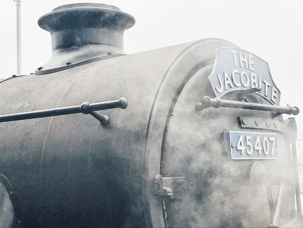 steam covering engine of jacobite train with livery and number