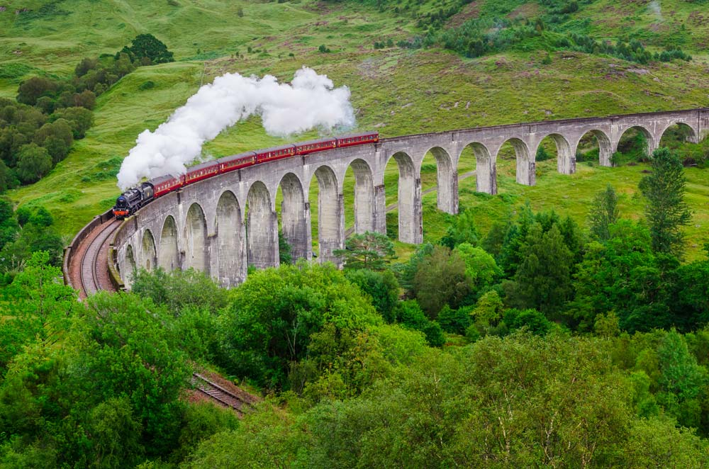 the jacobite steam train going over a curved viaduct known as the harry potter bridge