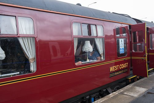 red exterior of jacobite steam train looking into 1st class carriage