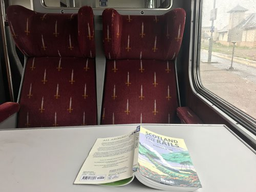 interior of vintage train carriage with book on table