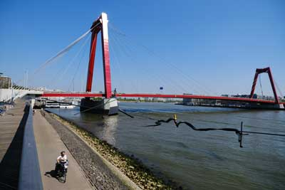 man cycling along river front with red bridge