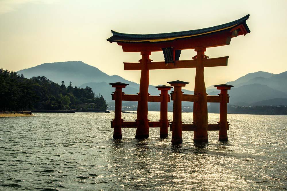 red tori gates in ocean at miyajima