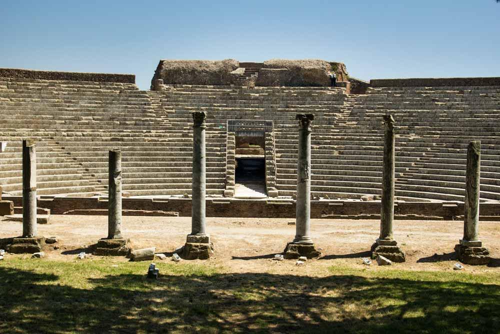 set of corinithian columns in front of roman amphitheatre
