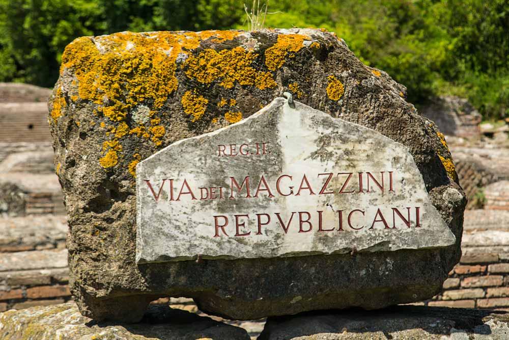 lichen covered stone with latin inscription at ostia antica
