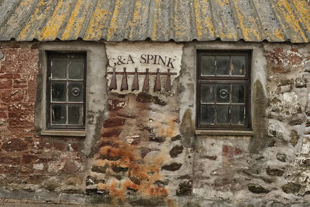 weathered exterior of stone building with metal sign with fish