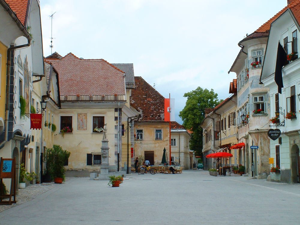 pastel coloured medieval buildings around town square in bled slovenia