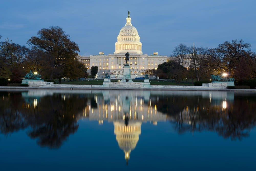 capitol building in us illuminated and reflected in water
