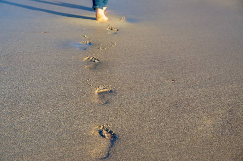 person leaving footprints in sand