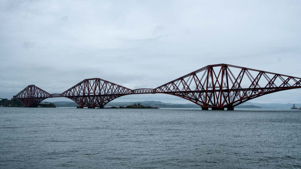 red iron cantilever bridge across wide river