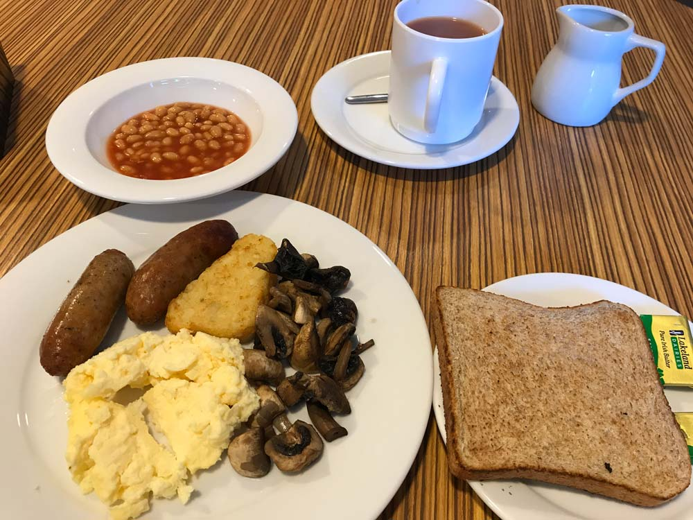 cooked breakfast with bowl of baked beans and mug of tea