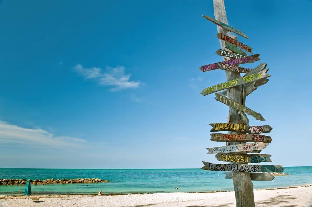 wooden signpost on beach under blue sky