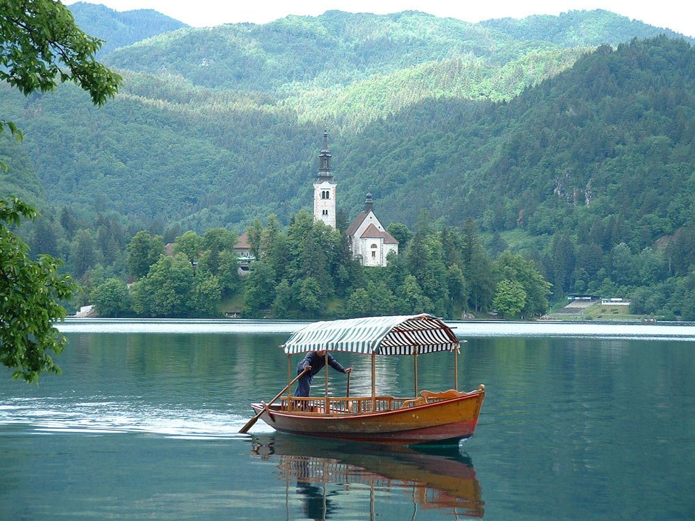 man rowing boat across lake with church in background