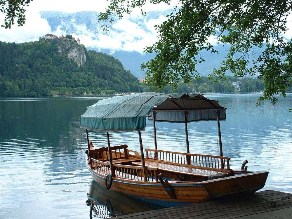 wooden boat by the side of lake bled