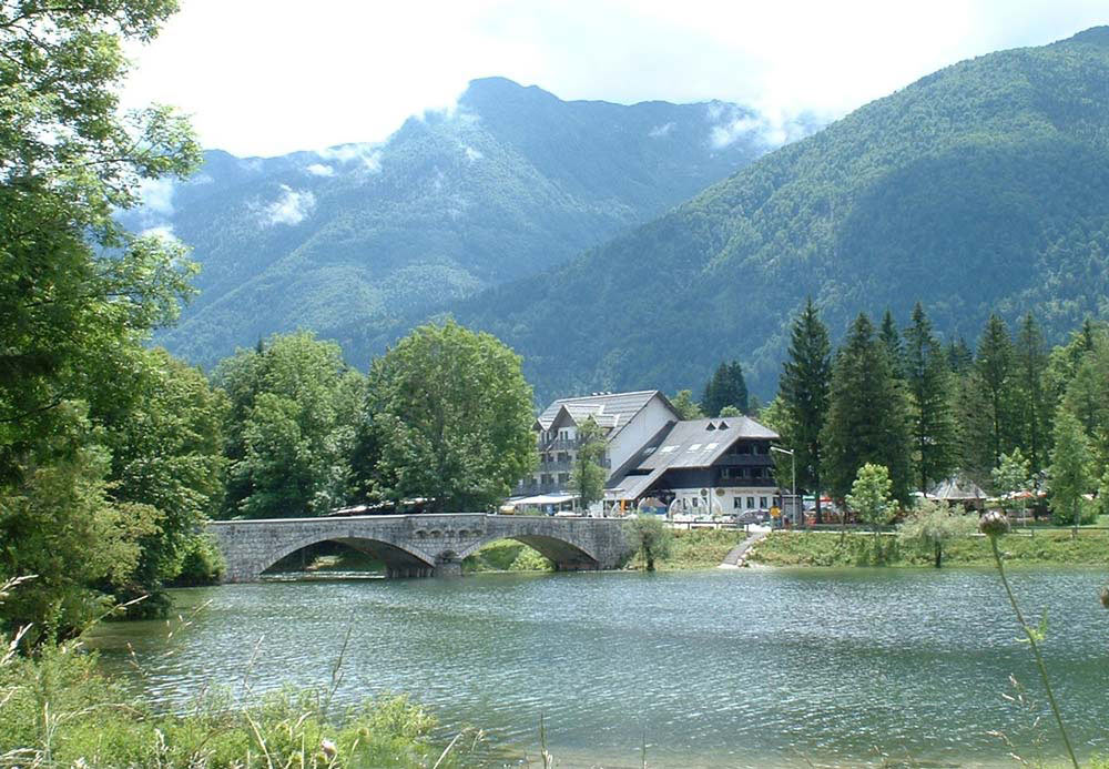 stone bridge across lake with mountains in background