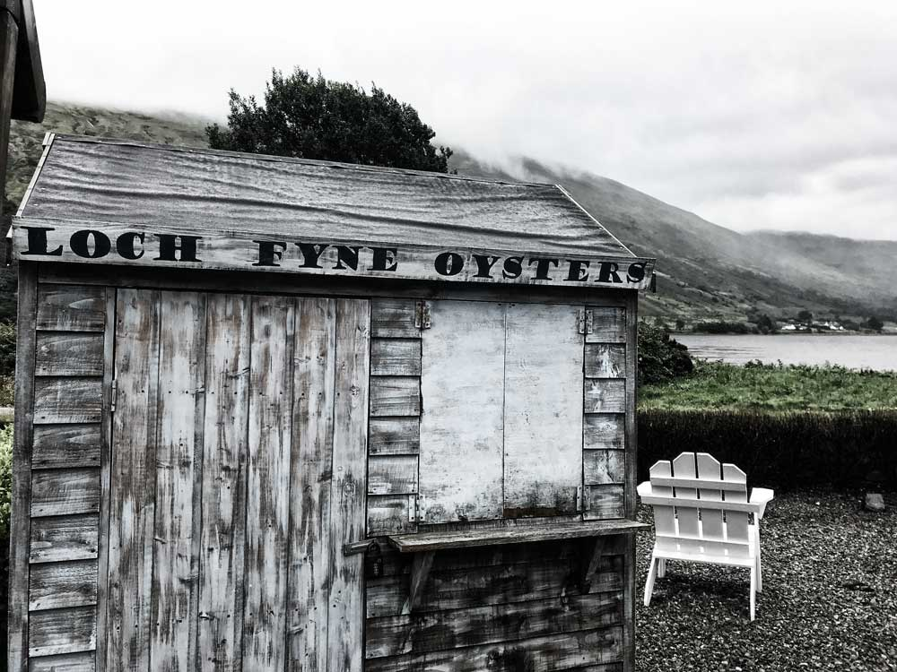 old wooden shack and chair at side of loch fyne in scotland