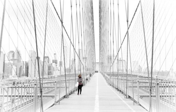 woman walking across the brooklyn bridge which is one pf the best places to travel alone in the usa