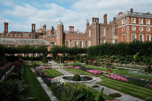 formal garden with pink flowers in front of red brick palace