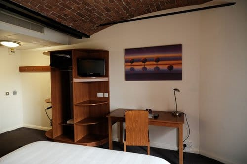hotel bedroom showing foot of bed with desk and shelves
