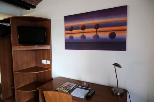 desk in hotel room with modern art hanging above and shelves with tv