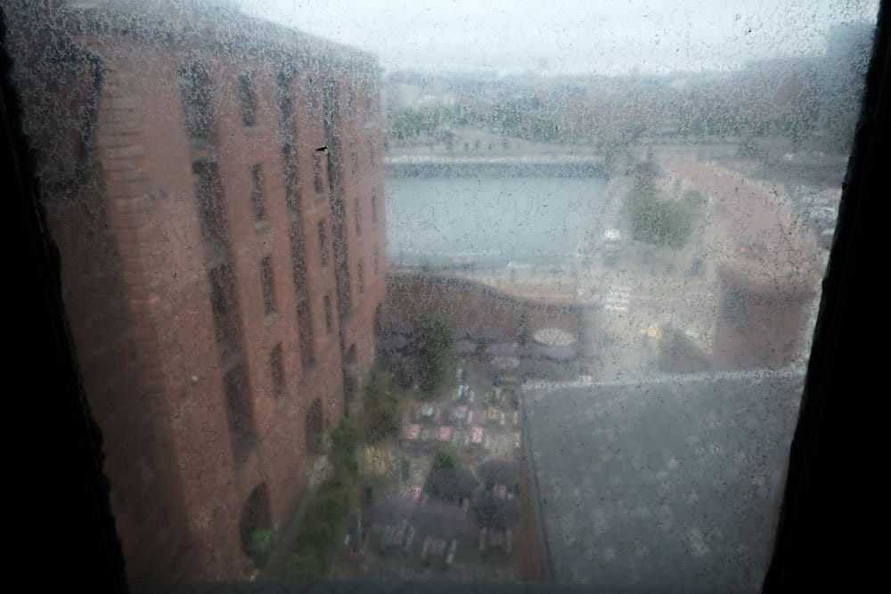 view of city and dock through a grimy window