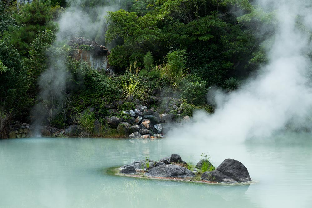 steaming hot spring set in forest