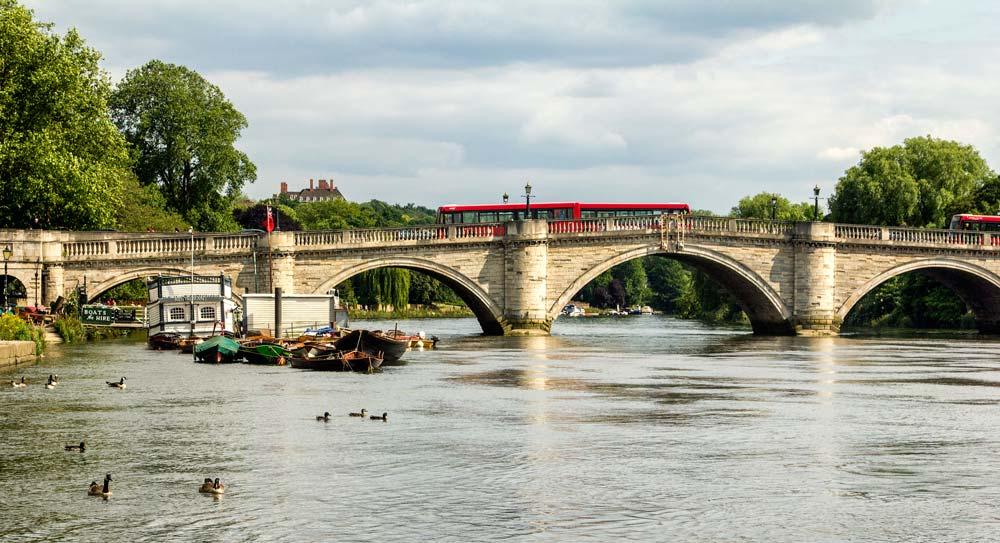 stone bridge with red double decker bus