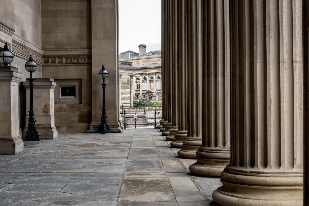 row of corinthian columns on a buildings portico with neoclassical building in distance