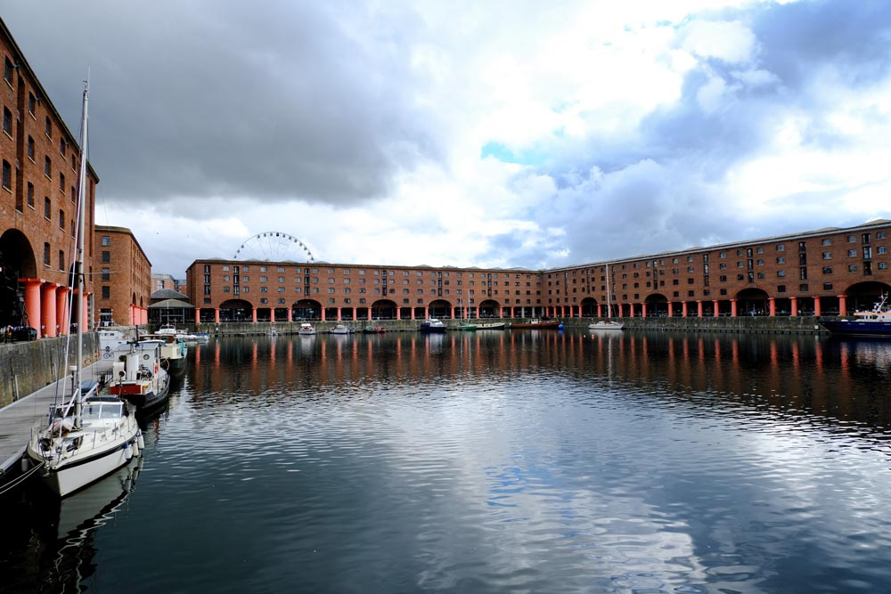 rows of red brick warehouse buildings reflected in the water of a dock