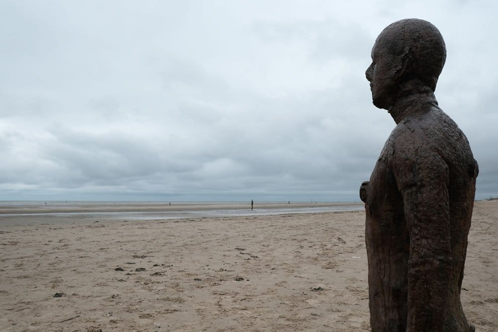 large statue of man on a sandy beach