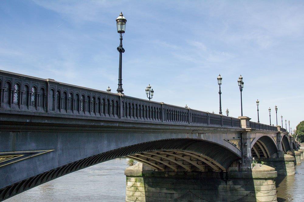 concrete bridge with lamp posts over river thames