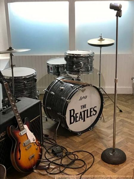 drum kit with the name of the beatles and a guitar