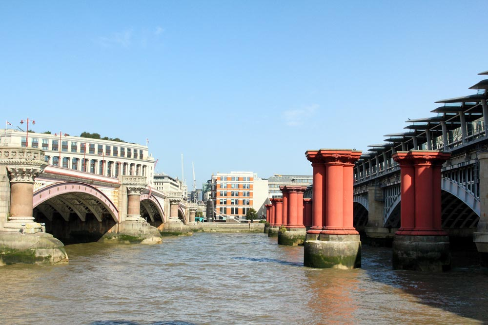 red columns of old bridge between two river bridges in london