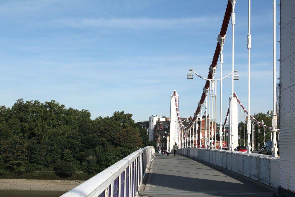 woman and dog walking across bridge in london