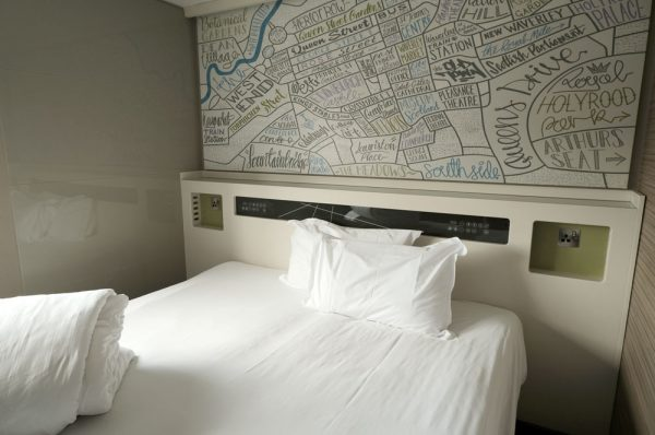 bed with white linen with large map above bed