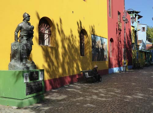 statue of soldier in front of a row of vibrant buildings