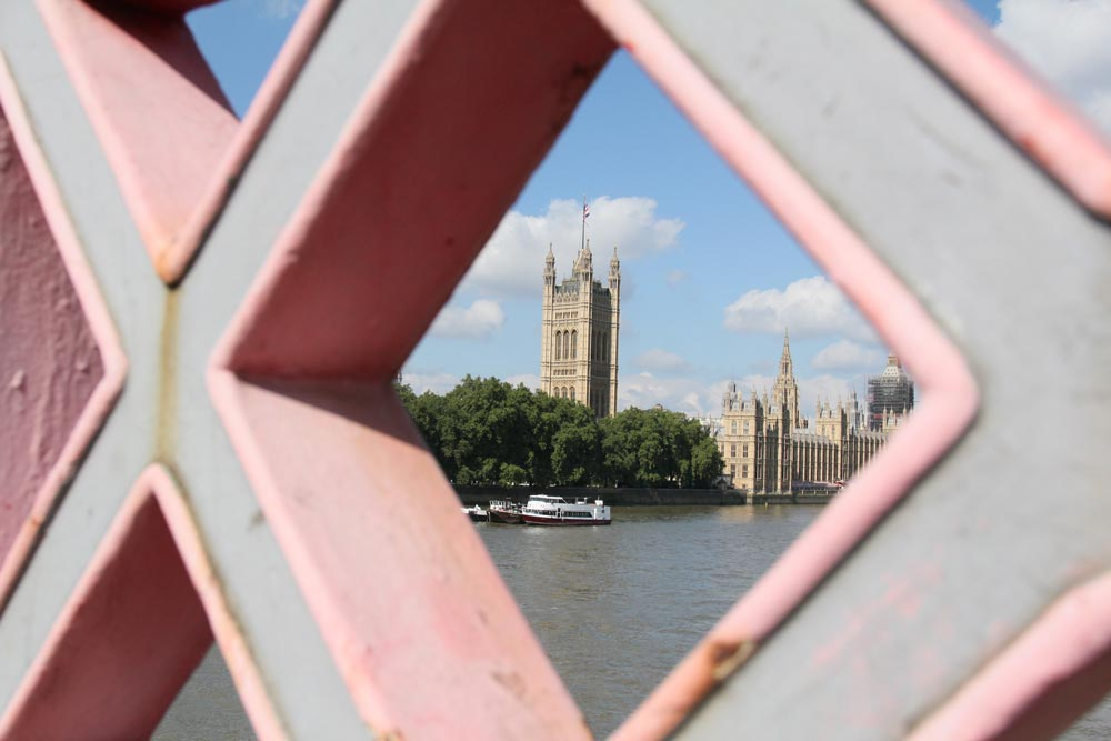 gothic tower and palace of westminster viewed through pink and grey opening