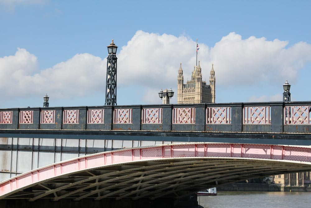 pink and grey bridge with gothic tower in background