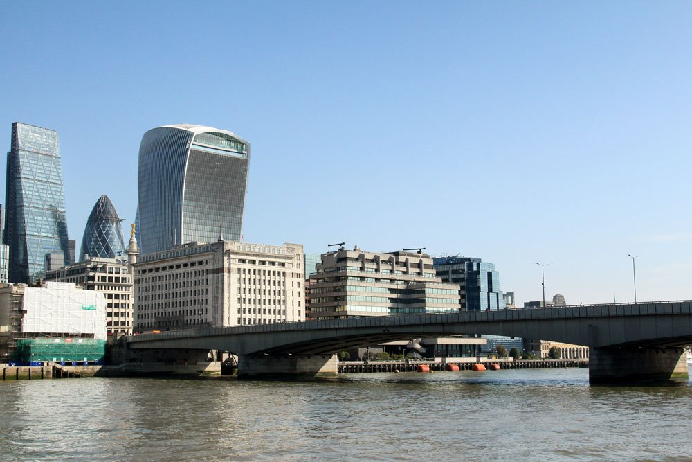 concrete london bridge over river thames with modern skyscrapers on bank