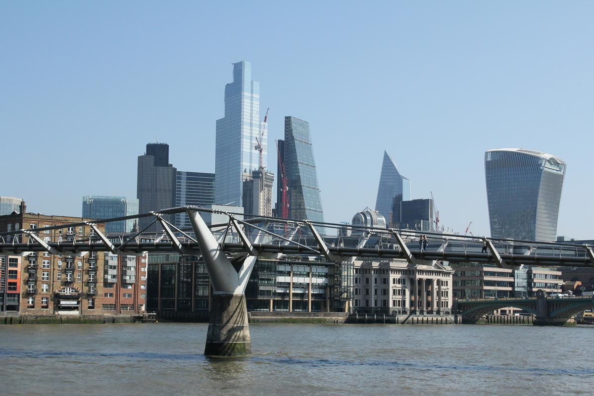 wooden footbridge in london across thames with skyscrapers in background