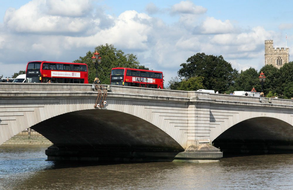 two red buses on stone bridge over river thames in london